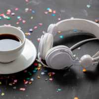 coffee cup next to headphones with confetti